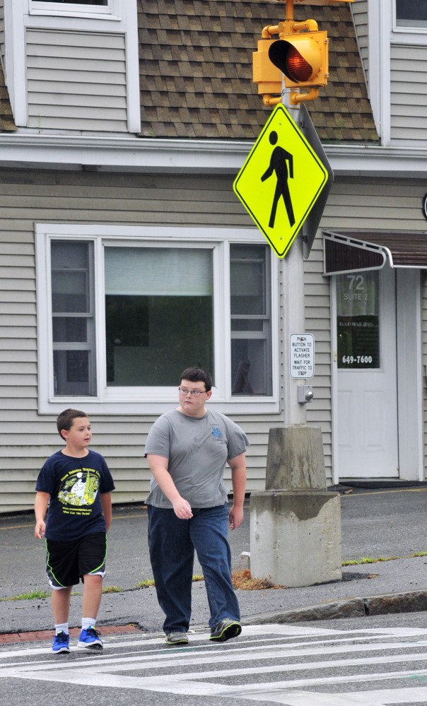 Keygan Wyman, 10, left, and his brother Ayden Wyman, 11, cross Western Avenue on Wednesday in the crosswalk where it intersects with Florence and Cushman streets. When school starts later this month, there won't be a crossing guard there like there's been in previous years.