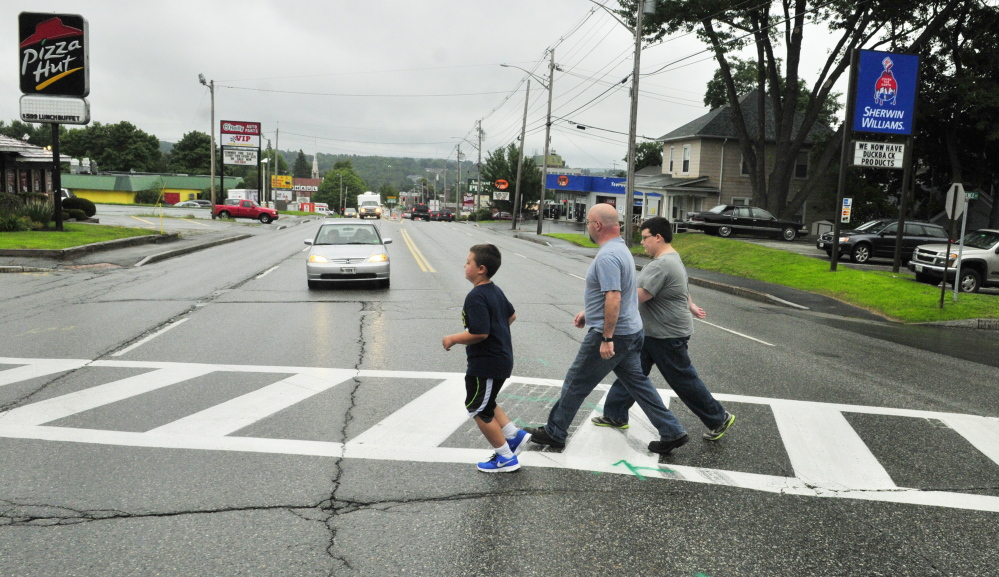 Jason Wyman, center, and his sons Keygan, 10, left, and Ayden, 11, cross Western Avenue on Wednesday in the crosswalk where it intersects with Florence and Cushman streets. When school starts later this month, there won't be a crossing guard there like there's been in previous years.