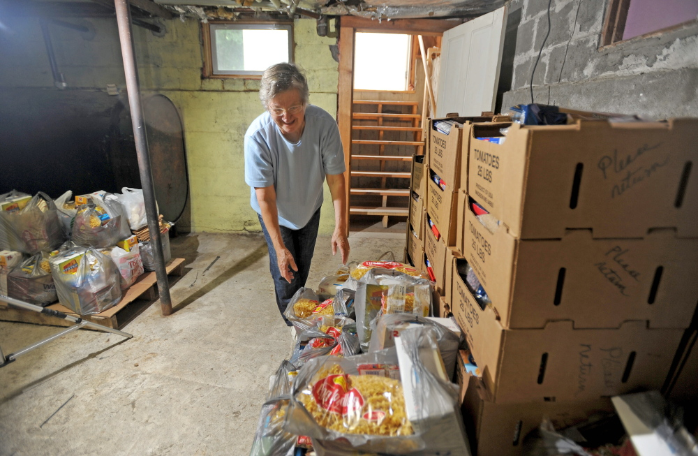 Louise Carl, food pantry coordinator at the Bingham Area Food Pantry, organizes the last pallet of donated food in the Bingham Area Food Pantry in the basement of St. Peter Church rectory in Bingham on Thursday. The pantry is shutting down after 33 years because the building is being sold.