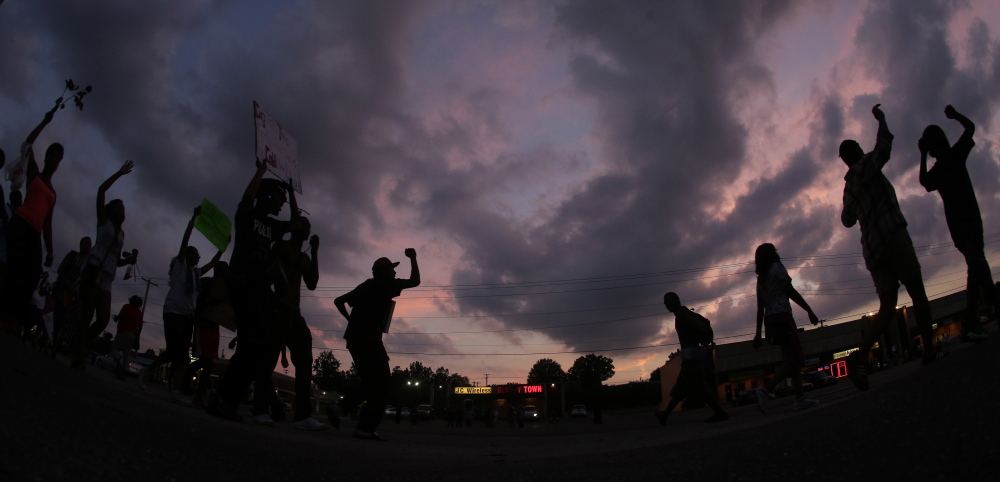 In this photo taken with a fisheye lens, people protest Monday, Aug. 18, 2014, for Michael Brown, who was killed by police Aug. 9 in Ferguson, Mo. Brown's shooting has sparked more than a week of protests, riots and looting in the St. Louis suburb. (AP Photo/Charlie Riedel)