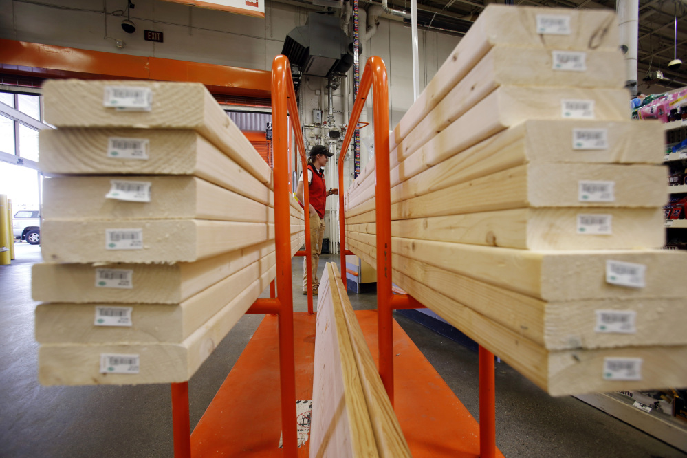 In this May 17, 2014 photo, a shopper checks out with her lumber at a Home Depot in Boston.