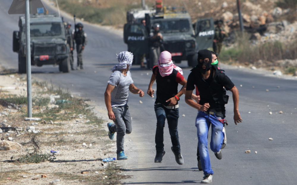 Palestinian protesters run away from Israeli soldiers during clashes following a demonstration against the Israeli military action in Gaza, in the West Bank city of Nablus on Friday.