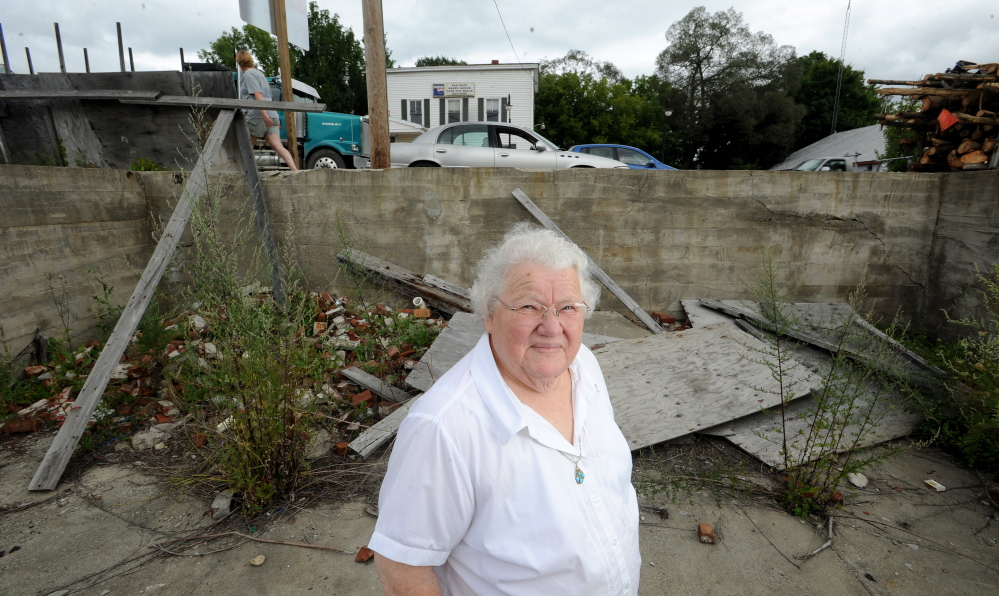Alice Emery stands in the foundations of two burned out buildings on Main Street in Norridgewock on Friday. Emery was housekeeper for Harold Alfond for 45 years and has taken on the mission to turn the eyesores into green space for the community.