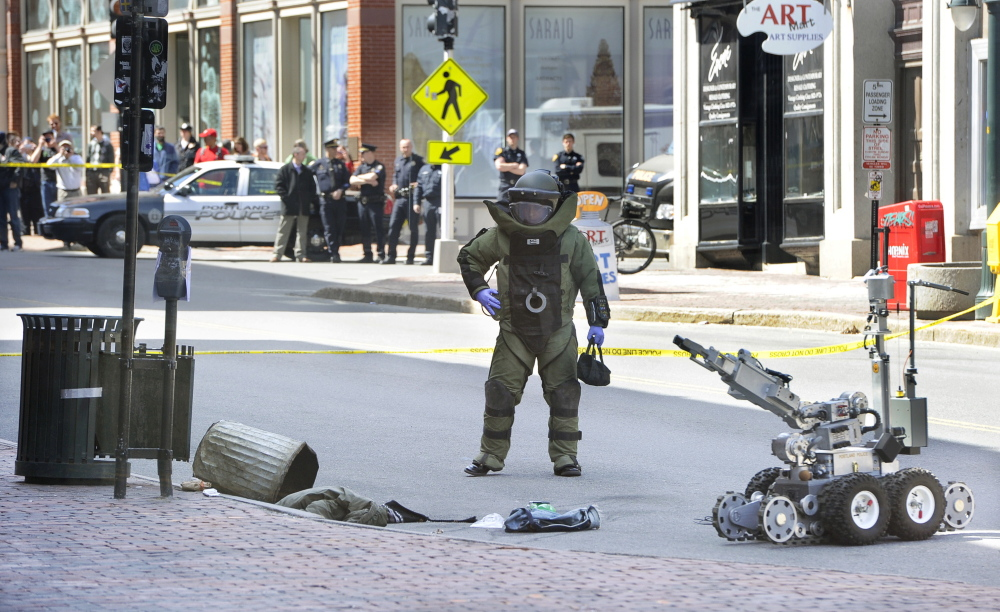 A Portland police bomb squad member uses a robot to remove a suspicious device from a trash can outside the CVS drugstore at 510 Congress St. on April 11, 2014.