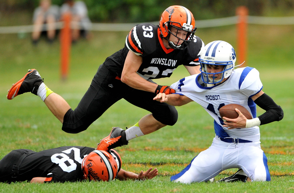 Madison High School quarterback Chase Malloy (11) is sacked by Winslow High School's Luke Fredette (28) and Ryan Fredette (33) during the Black Raiders' 38-7 win Saturday at Poulin Field in Winslow.
