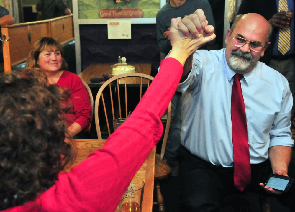 Augusta mayoral candidate Dave Rollins, right, high-fives his wife, Jan Rollins, on Tuesday night at Lisa's Restaurant and Catering in Augusta after election results come in. Rollins won the election.