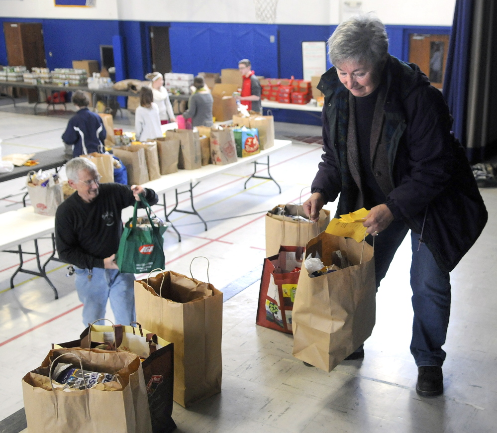 Judge Rae Ann French organizes food baskets Sunday on the stage of St. Michael School that her husband, Fern LaRochelle, left, helped pack. The couple have been helping prepare Thanksgiving baskets at the Augusta school for several years.