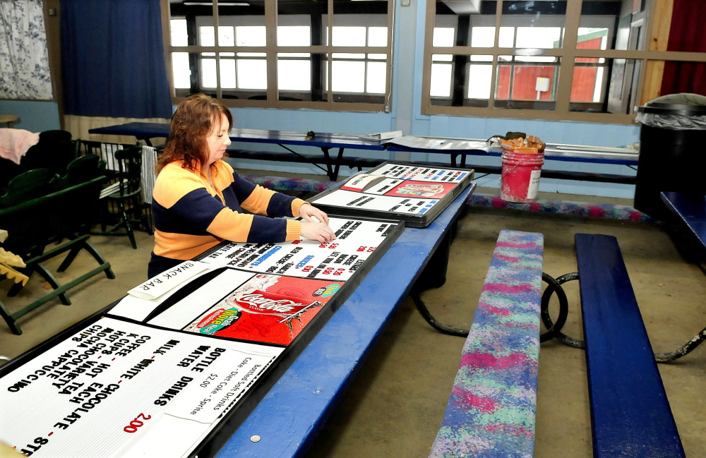 Eaton Mountain Ski Area manager Julie Keaten works on a menu board in the lodge that is undergoing renovation at the Skowhegan resort on Sunday.