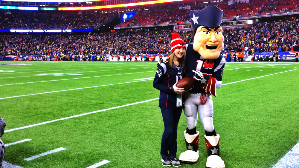 Bethany Hammond, of Belgrade, poses with Pat Patriot, the official mascot of the New England Patriots, before the AFC Championship game Sunday.