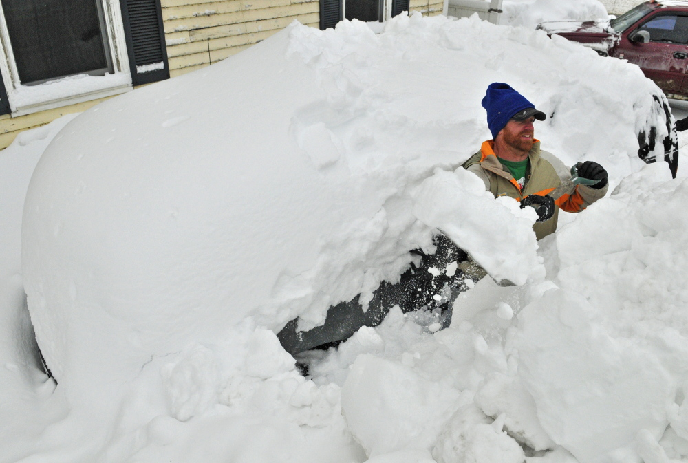 Nick Smith throws snow onto a pile that's over his head Thursday while excavating a sport-utility vehicle that had been stored outside all winter in Hallowell.