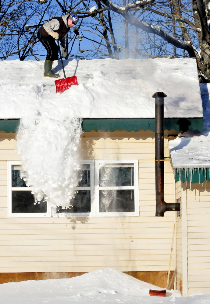 """Bob Foster shovels snow from the rooftop of his home in Benton last Sunday. """"I like to stay on top of this snow,"""" Foster said. More fell during the week, and Foster will have even more to deal with after forecast that there may be as much of a foot of new snow by Monday."""