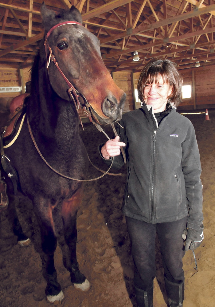 Debbie Hight stands with Postcard Jack, who has retired from harness racing and is training to be a saddle horse, on March 31.