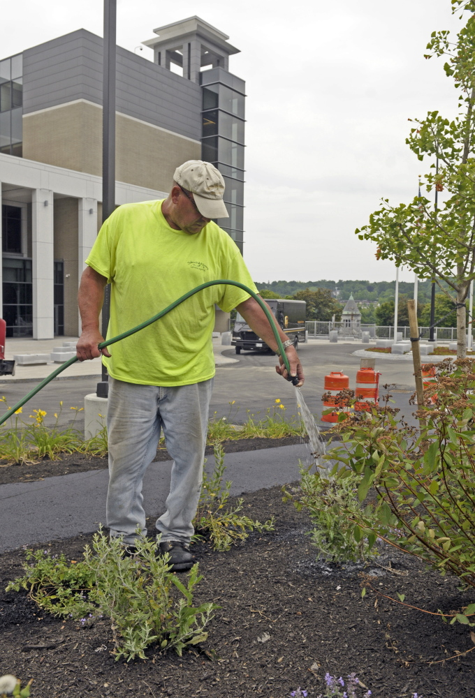 Bruce Battersby, of Salmon Falls Nursery and Landscaping in Berwick, waters new plants Thursday at the Capital Judicial Center in Augusta.