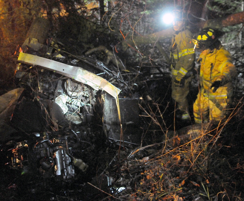 Firefighters search a vehicle Nov. 5, 2014 that rolled over on the Plains Road in Readfield, killing a passenger.