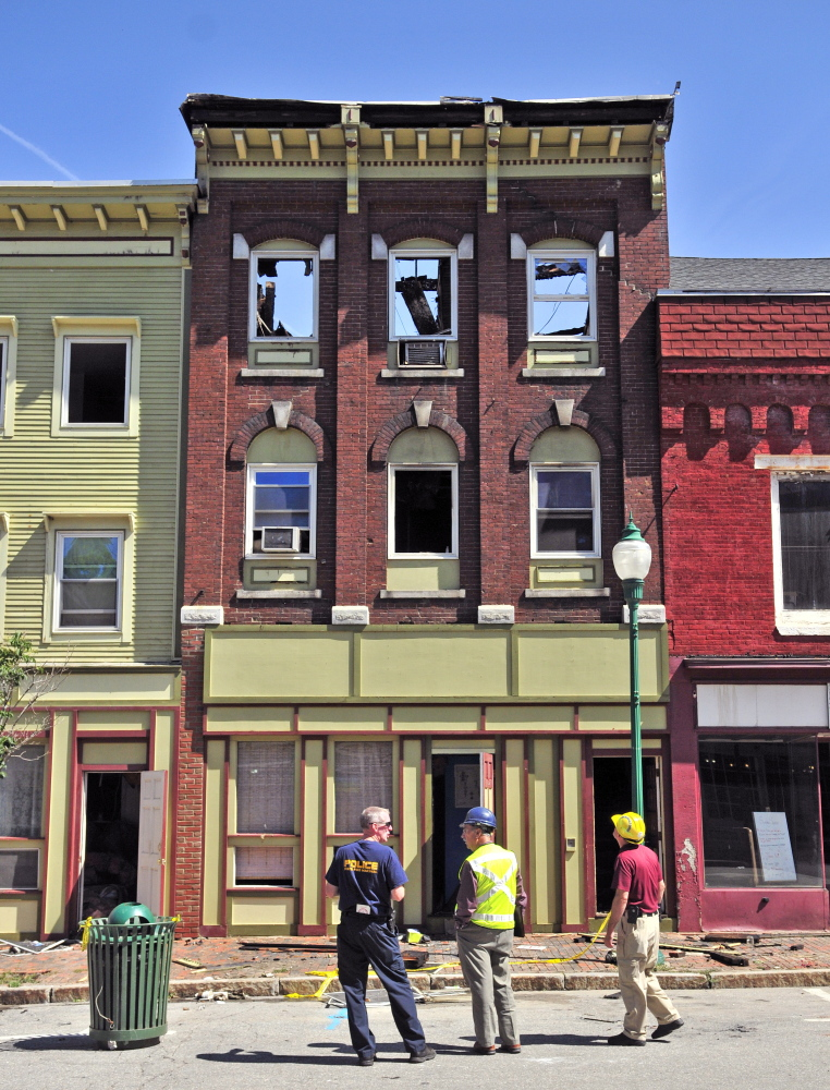 Officials stand in front of the scene the morning after the July 16 fire in downtown Gardiner.