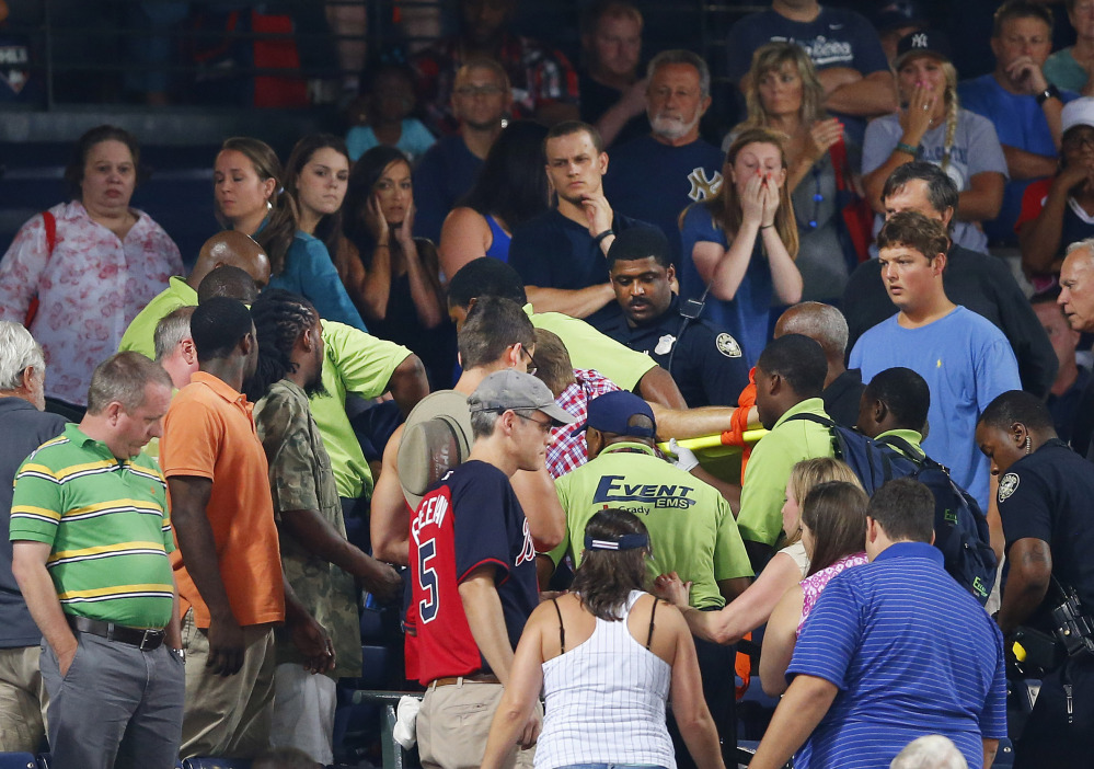 Rescue workers carry an injured fan from the stands at Turner Field during a baseball game between Atlanta Braves and New York Yankees, Saturday in Atlanta.