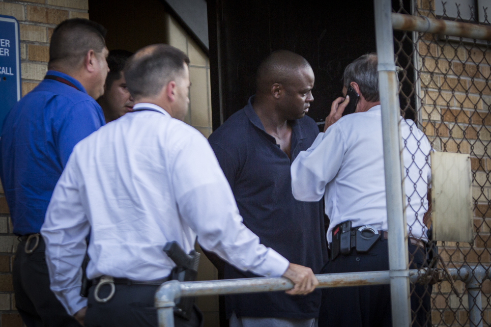 Shannon J. Miles, 30, is walked out of the Harris County Sheriff's Department in Houston on Saturday.