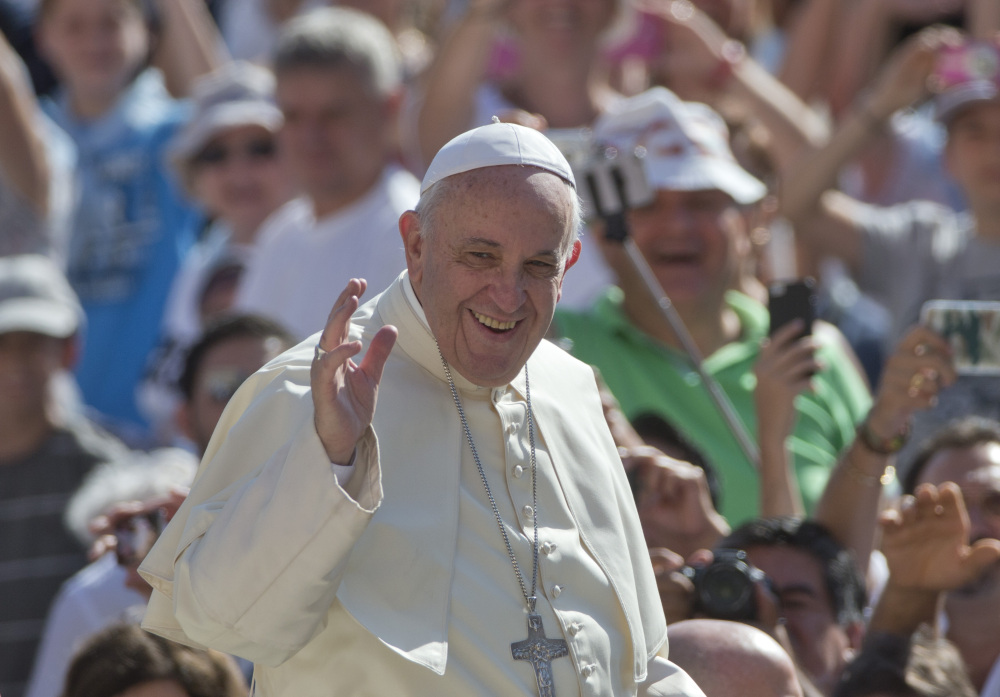 In this Wednesday, Aug. 26, 2015, file photo, Pope Francis waves as arrives for his weekly general audience in St. Peter's Square at the Vatican.