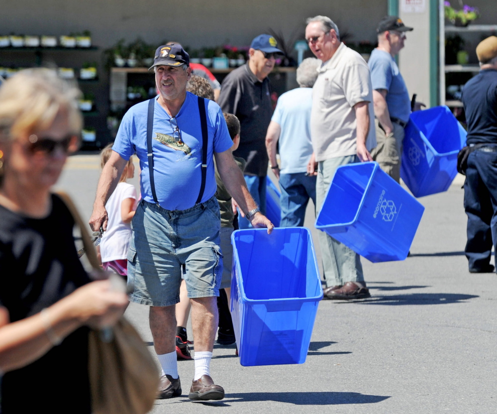 People make their way back to their vehicles with free recycling bins from Ecomaine at Elm Plaza in Waterville in June 2014. The program is part of the city's pay-as-you throw trash program that began a year ago.