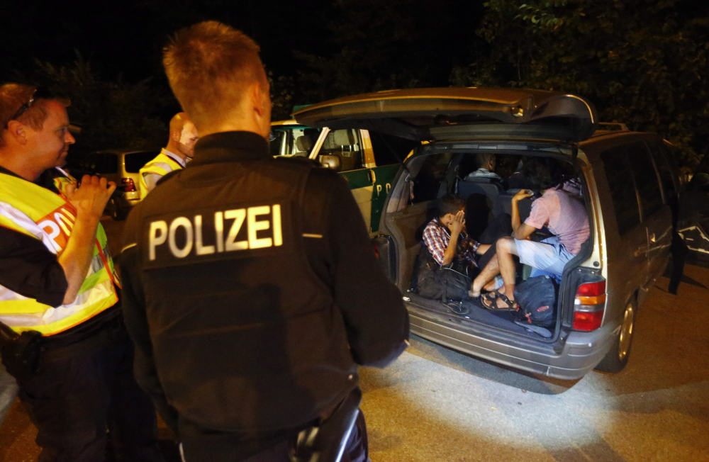 A group of migrants from Syria sits inside a vehicle stopped by German police on a country road heading to Freilassing, Germany, from Salzburg, Austria, on Sunday, as Germany imposed border controls to cope with thousands of migrants.