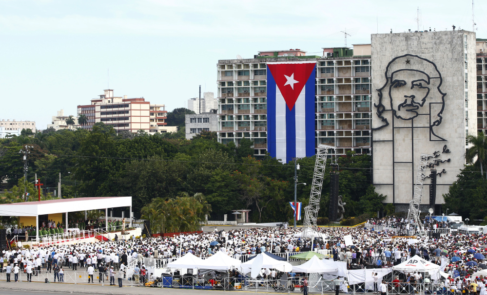 """People gather in Revolution Square as Pope Francis celebrates Mass in Havana, Cuba, on Sunday, where a sculpture of revolutionary hero Ernesto """"Che"""" Guevara and a Cuban flag decorate government buildings."""
