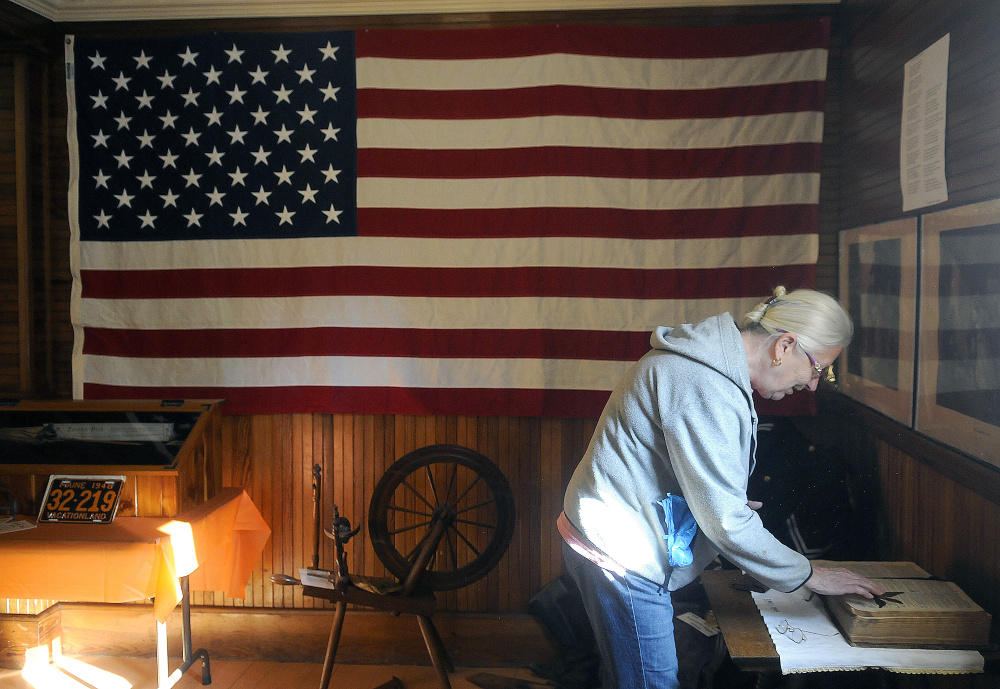 Linda Cobb unfolds a Bible at the Manchester Grange Thursday in preparation for a display by the Manchester Historical Society on Sunday.