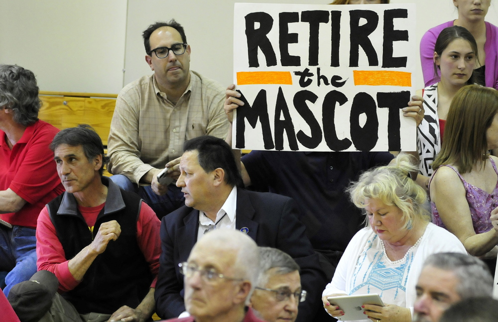Mark Roman holds a sign is support of changing the Skowhegan High School team mascot during a forum in Skowhegan in May. At far left is former chief of the Penobscot tribe Barry Dana of Solon. A group supporting keeping the nickname plans a Skowhegan Indian Pride rally on Columbus Day, while Maine Indians and their supporters are holding an Indigenous Peoples Day rally at Lake George in Skowhegna. The events are the latest surrounding the last school in the state that has Native American imagery.