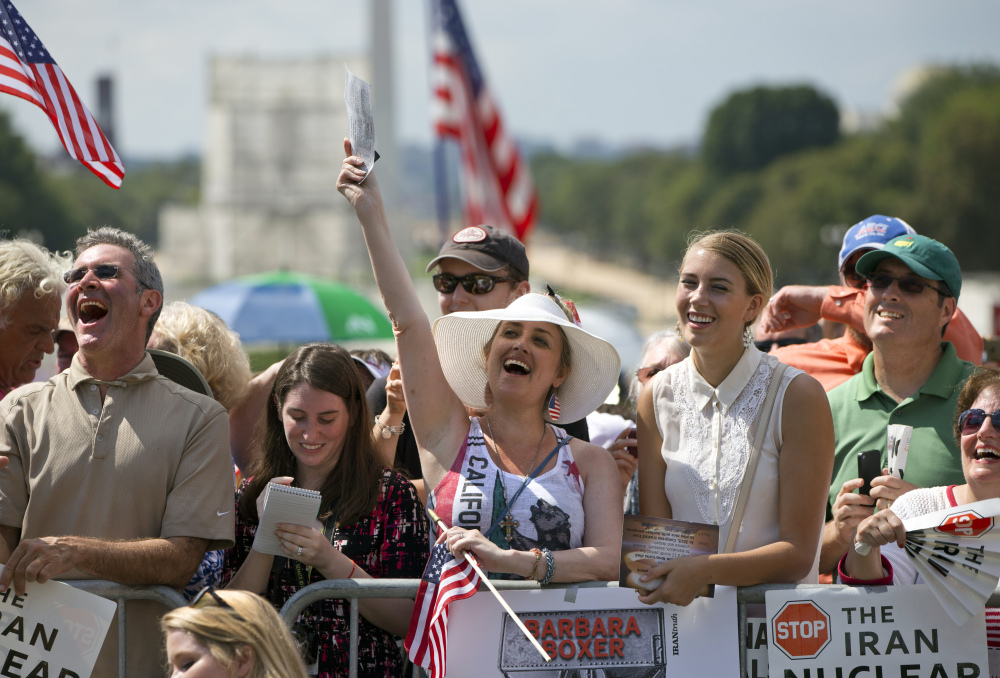 """Kimberlee Crawford of Los Angeles, center, cheers as she attends a rally – led by Donald Trump and Ted Cruz – against the Iran deal Wednesday outside the Capitol in Washington. """"We are led by very, very stupid people,"""" Trump said. """"We cannot let it continue."""""""