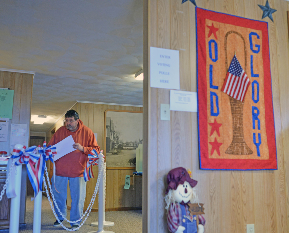A voter leaves the polls with his ballot after voting at the Anson Town Office on Tuesday.