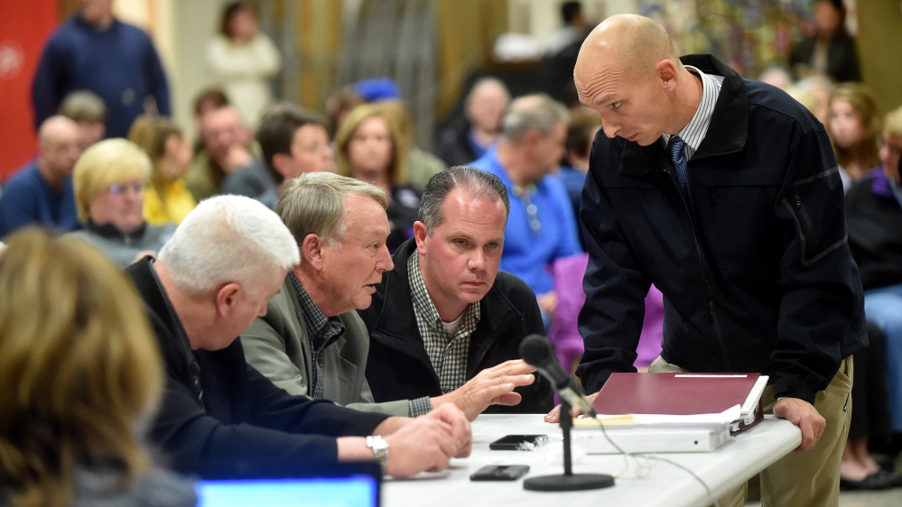 Eric Haley, left center, superintendent of schools in Waterville confers with Waterville police detectives Dave Caron, right center and Bill Bonney, far right, during an open session hearing about allegations Waterville Senior High School principal Don Reiter asked a student for sex at George J. Mitchell School in Waterville on Wednesday.