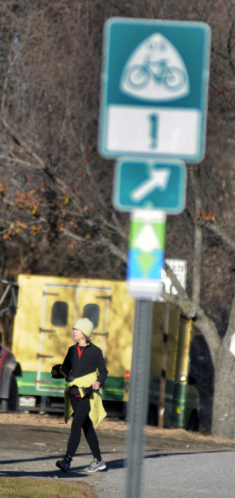 Pat Connors exits the Kennebec River Rail Trail Monday near her home in Hallowell. Signs marking the East Coast Greenway bike trail have gone up in Augusta and Hallowell recently, as the trail continues to try to expand its reach through all of Maine and down to Florida.