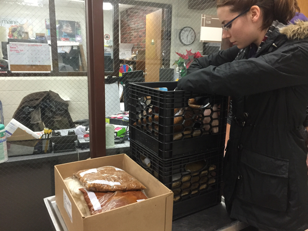 Catherine Dufault sorts through crates of vegetables, rice and Beef Stroganoff recovered from the Aramark dining service at UMF, as part of the UMF chapter of the Food Recovery Network she established to reduce food waste and help the hungry in Franklin County.