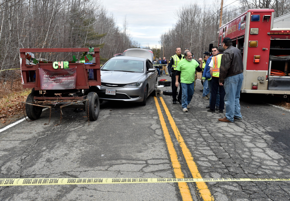 Rescue workers from Waterville fie department and Delta Ambulance tend to multiple victims involved in a car versus horse-drawn carriage collision on Industrial Road in Waterville on Friday.