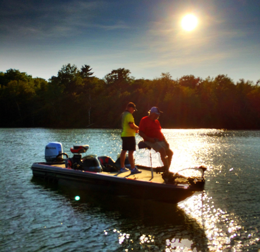 """Ted Thibault of fishing equipment firm Tuf-Line and Charlie Ingram of the Outdoor Channel show """"Fishing University"""" cast their lines in China Lake during a September sunset during an episode taping of the show. The episode airs this weekend."""