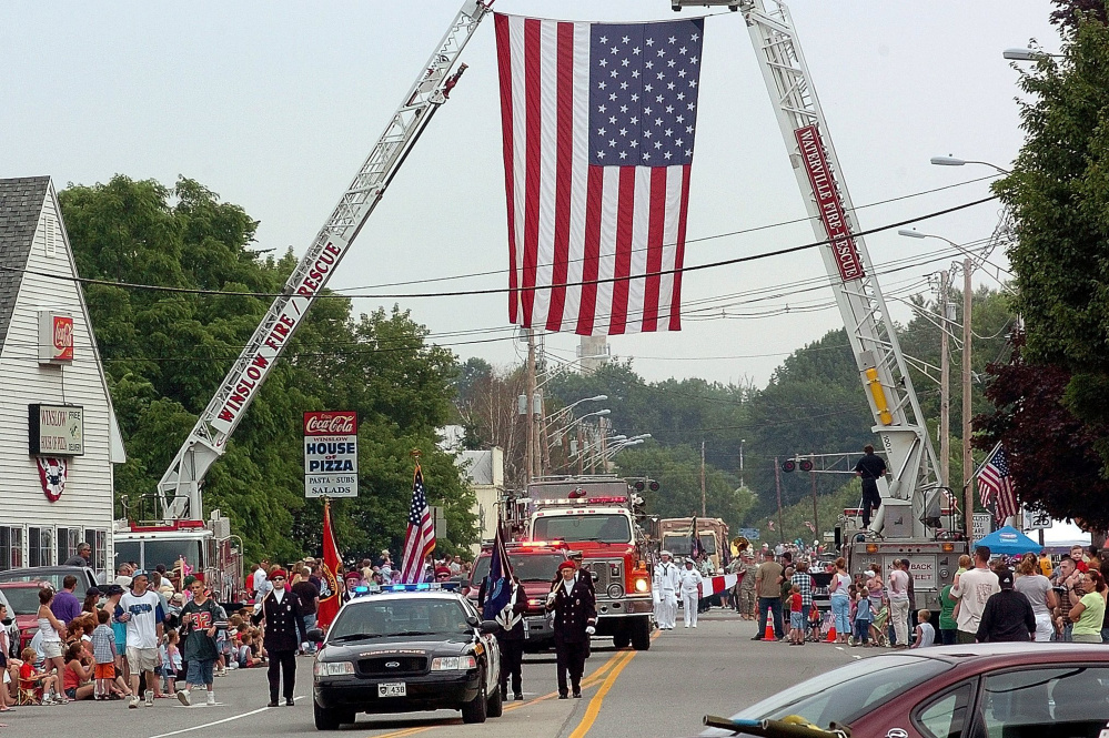 Participants of a previous Winslow Family 4th of July parade pass under a huge American flag on Bay Street suspended by ladder trucks from the Winslow and Waterville fire departments. Town officials have settled on a new plan for police coverage that draws on other agencies in central Maine to help cover the event that attracts thousands of people.