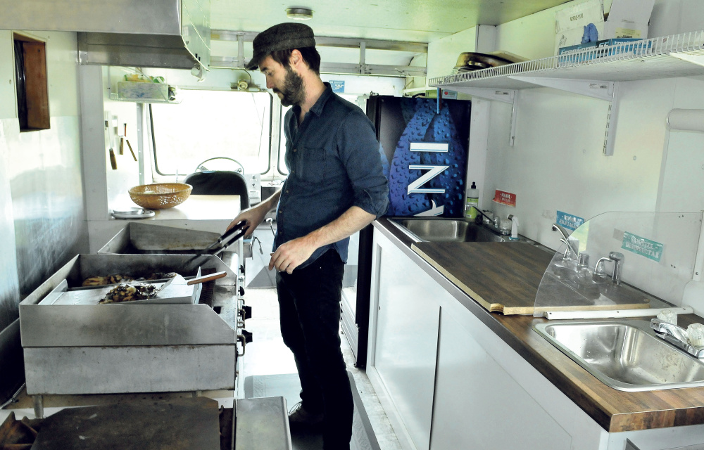 Garnet Keim cooks chicken and mushrooms in his food truck, El Toro, on Tuesday in Weld. The Weld native and his wife, Anne Holloway, moved back to the family farm five years ago, The couple's food truck is expected to debut this weekend.