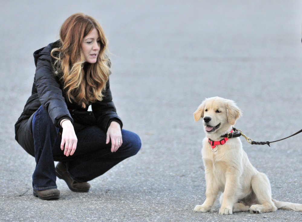 AmyLou Craig, left, and her puppy, Brewer, on Nov. 24, 2015, in a parking lot near the Kennebec River Rail Trail in Augusta following the incident in which she says a man kicked the puppy.