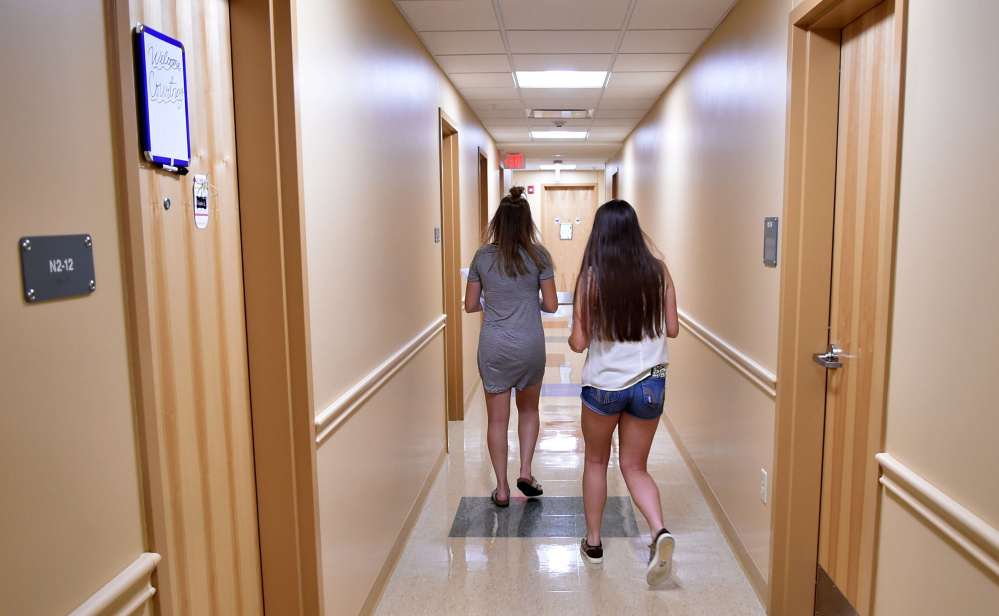 Taylor Peno, left, and Makenzie Carlow walk down a hallway Friday at Hinman Hall at Thomas College in Waterville after moving into their room.