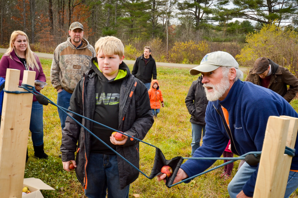 """Lukkas Whitman, of Clinton, learns from Mark """"Mac"""" McAfee, of Belgrade, how to use the apple slingshot Saturday at the Fall Festival on Saturday at the Quarry Road Trails recreation area in Waterville."""