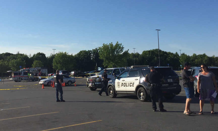 Crime scene tape surrounds a Volkswagen Jetta June 26 in a parking lot at the Wal-Mart store in Augusta as police officers look for evidence after a report of shots fired at the site.