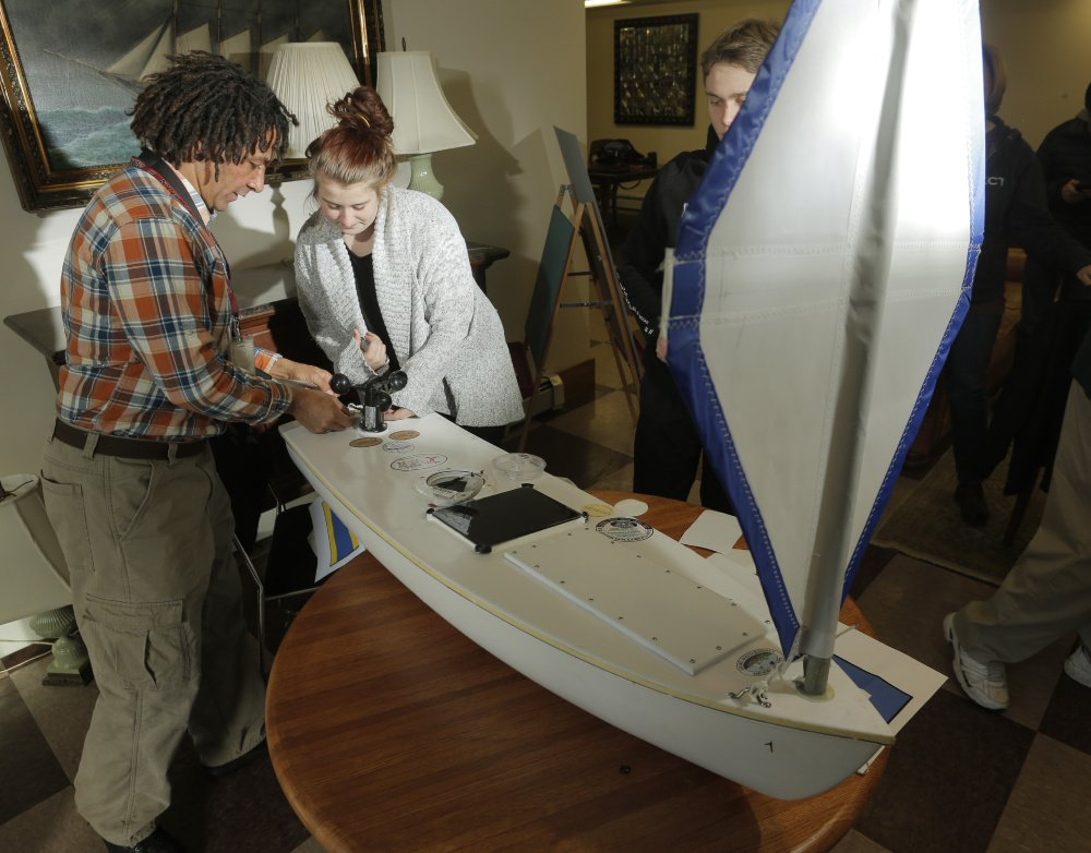 Teacher Ed Sharood, left, and junior Kristin Cofferen, of Kennebunk High School's Alternative Education Class, apply stickers from local businesses on a small boat that they hope will reach Ireland after it is launched. At right, behind the sail, is senior Josh Ellis, who was the boat project manager.
