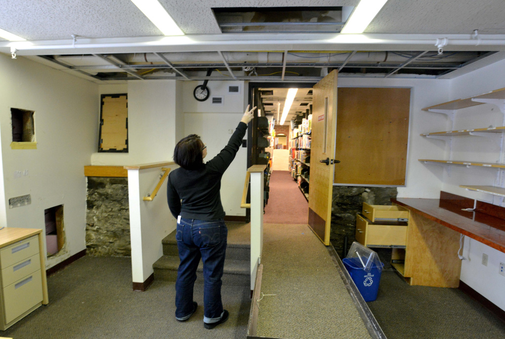 Tammy Rabideau, assistant director at the Waterville Public Library, points on Saturday to a pipe that broke overnight in the library. Water spilling from the pipe damaged books and computers the library.