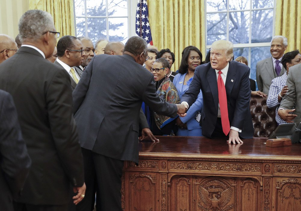 President Trump shakes hands with leaders of the nation's historically black colleges and universities in the Oval Office on Monday. Leaders of the schools were there to press their case for greater attention from the new Republican administration.