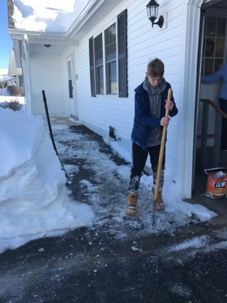 Hunter Gagne, 13, picks away at ice Friday in front of Eisa Thibeau's condominium in Winslow.