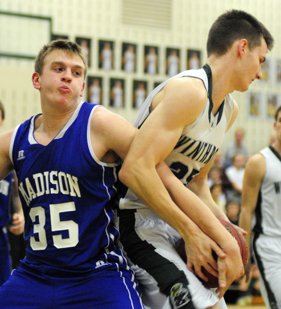 Madison's Max Shibley, left, fights for a rebound with Winthrop's Garrett Tsouprake during a game earlier this season in Winthrop.