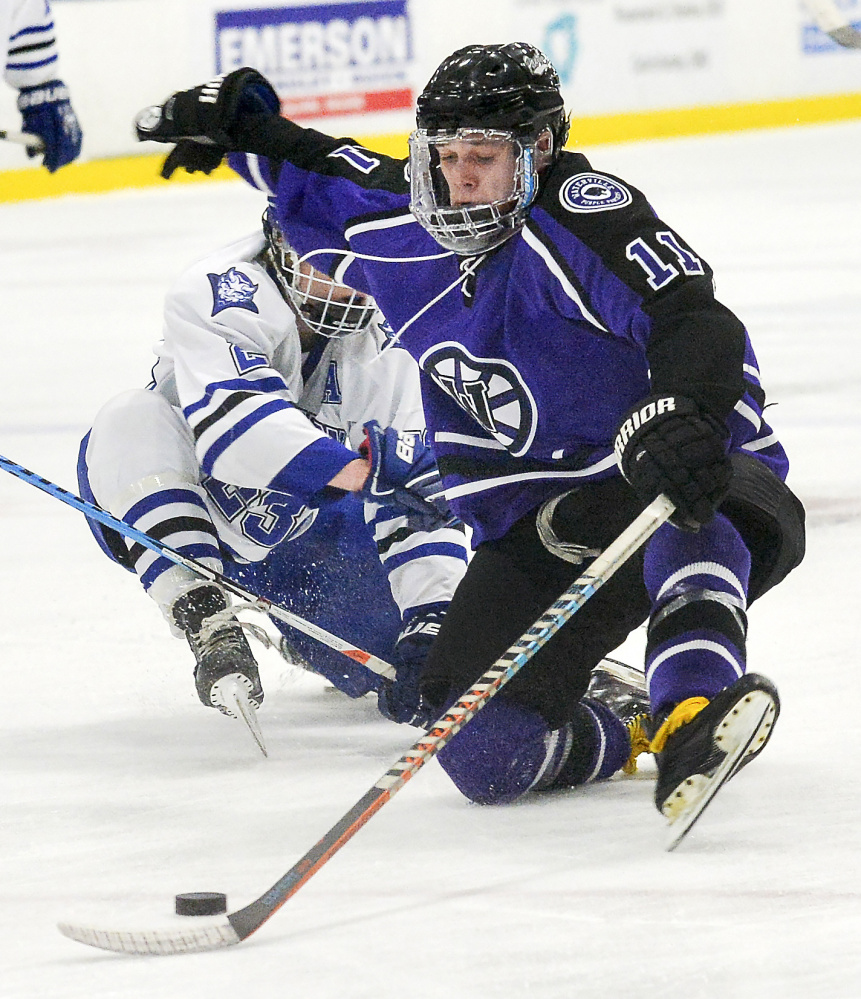 Waterville's Jackson Aldrich maintains control of the puck after being knocked to the ice by Lewiston's Brad McLellan Tuesday night in Lewiston.