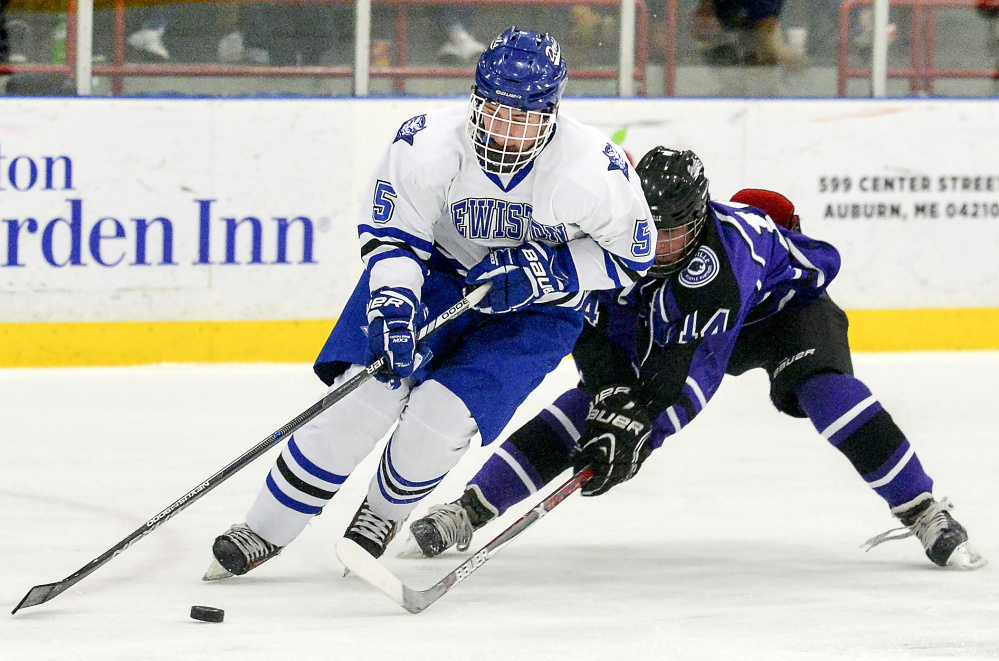 Michael Bolduc fights for control of the puck with Lewiston's Sam Story in the first period of their game Tuesday night in Lewiston.