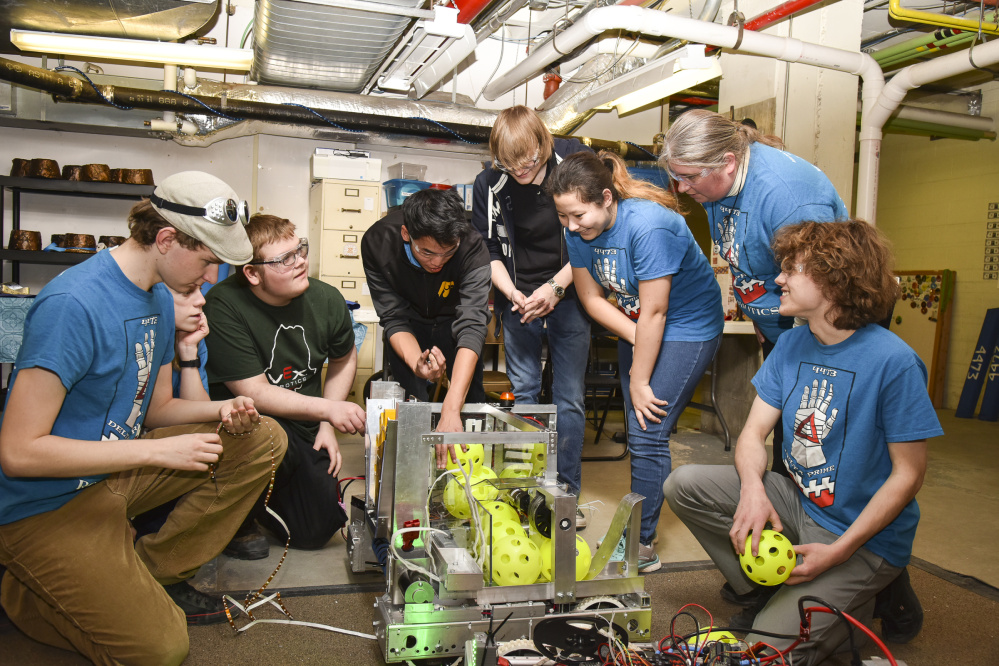 Hall-Dale High School students, all members of Delta Prime Robotics, huddle around their robotic entry Tuesday at the Ballard Center in Augusta with mentor Karen Giles, second from right, in order to finish their work before the competition deadline. The students are, from left, Kieran Dionne, Eli Spahn, Michael Crochere, Ean Smith, Bryce Bradgon, Alicia Warren and, at far right, team business and coding captain William Fahy.