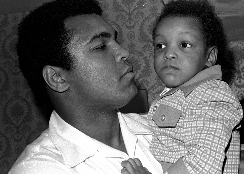 Heavyweight boxing champion Muhammad Ali, and Little Muhammad Ali, his 2 1/2 year old son, arrive at Miami Beach, Florida, in 1975. Ali's son, who bears the boxing great's name, was detained by immigration officials at a Florida airport Saturday and questioned about his ancestry and religion in what amounted to unconstitutional profiling, a family friend said.