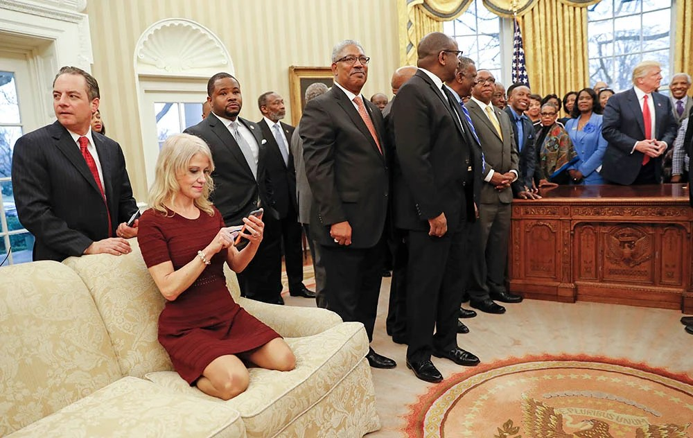Counselor to the President Kellyanne Conway looks at her cellphone while President Trump meets with leaders of Historically Black Colleges and Universities in the Oval Office  Monday. Also at the meeting are White House Chief of Staff Reince Priebus, left.